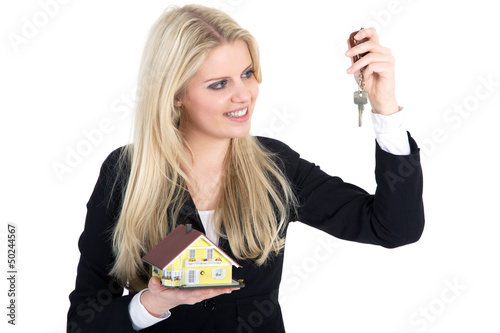 Junge blonde Frau freut sich über Schlüssel für Haus