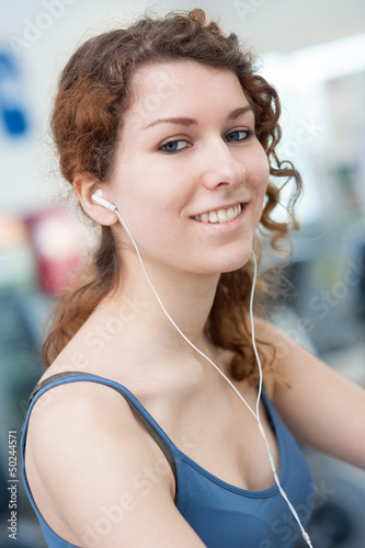 Young woman portrait in the gym while listening to music.