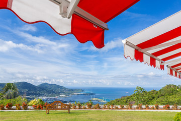 Awning over bright sunny blue sky with bench and sea view .