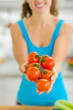 Closeup on bunch of tomato in hand of young woman