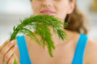 Closeup on young woman smelling fresh dill