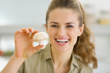Happy young housewife holding mushroom in kitchen
