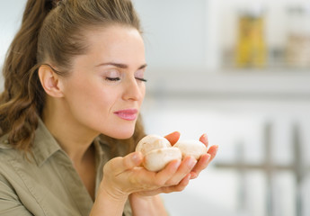 Young housewife smelling mushroom in kitchen