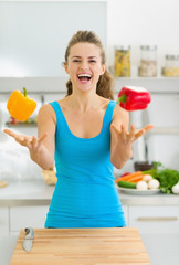 Happy young woman juggling with bell peppers in kitchen