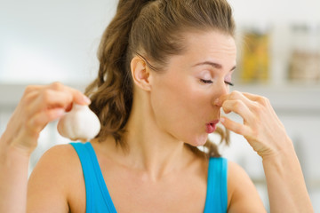 Young woman holding smelly garlic