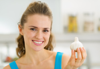 Smiling young housewife showing garlic