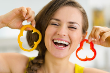 Happy young woman using slice of bell pepper as earrings