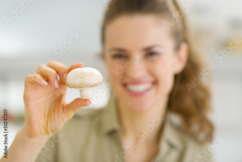Smiling young housewife holding mushroom in kitchen