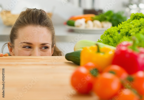 Young woman looking out from cutting board