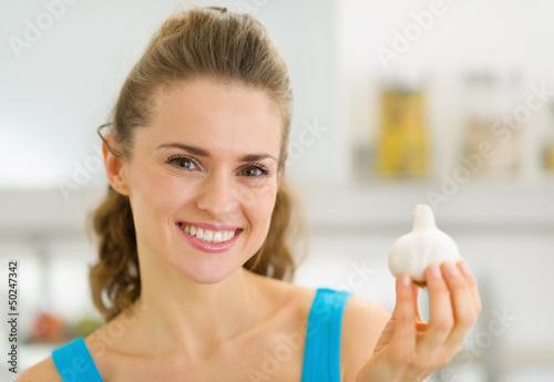 Smiling young housewife showing garlic
