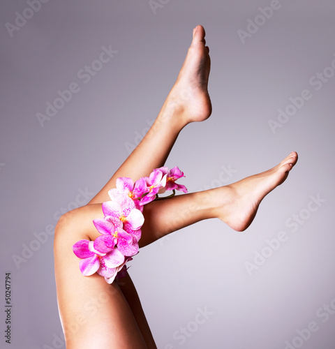 Beautiful slender female legs with flower