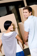 Back view of happy couple carrying cardboard boxes
