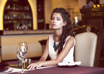 Dreaming Woman waiting at Decorated Table in Restaurant Interior