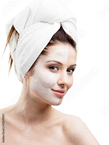 Woman in headband with cream applied on a half of her face