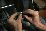 Goldsmith polishing silver ring with his old hands poster