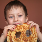 Cute boy is eating pancake