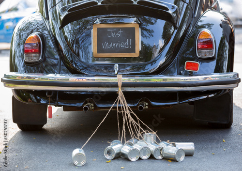 Rear view of a vintage car with just married sign and cans attac
