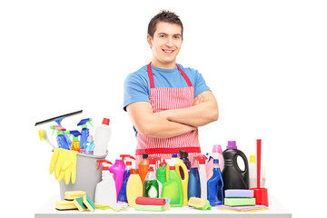 Young man in apron posing with cleaning supplies