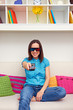 woman sitting on the sofa and watching 3d film