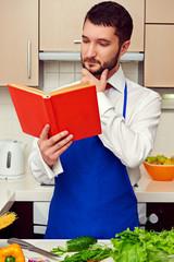 man in blue apron reading cookbook