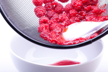 sieving raspberries for jam