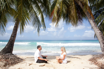 couple meditating in tropical beach