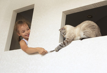 Little girl plays with a striped cat.