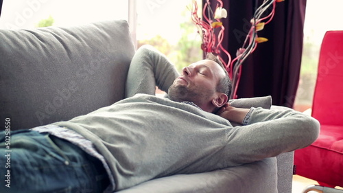 Young man taking nap on sofa at home