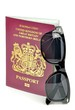A British passport and sunglasses on a white background
