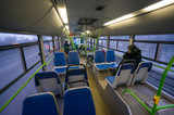 Interior of modern city bus with passengers in evening. Shot fro