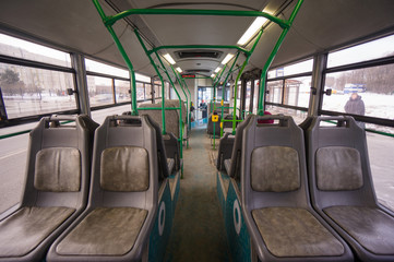 Interior of modern city bus on bus stop. Shot from back side of