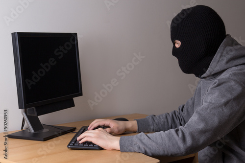 masked man with computer in office
