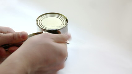 Man opening metal can with tomato sauce with vintage key
