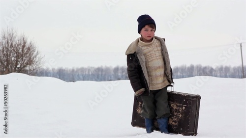 boy with a suitcase in winter