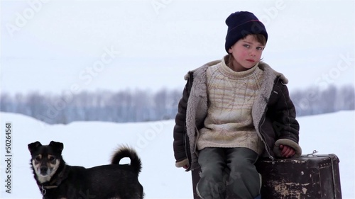 boy with a suitcase and a dog in winter portrait