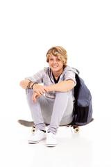 happy teen boy sitting on skateboard isolated