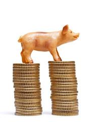 Zwei Stapel aus Euro-Münzen mit Schweinchen Figur