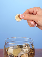 Saving, female hand putting a coin into glass bottle,