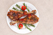 Roasted turkey legs on white plate with cherry tomato and rosema