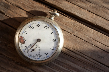 Old pocket watch on wooden background.