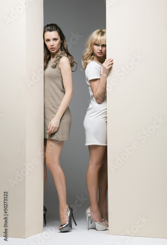 Attractive women hiding theirselves behind the wall