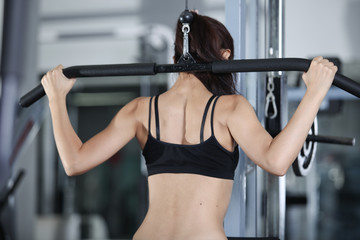 Woman at the gym doing exercises to strengthen muscles of back