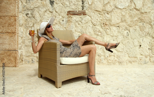 wealthy woman on a rattan chair