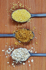 Brown rice, oatmeal, millet in spoons on the wooden background