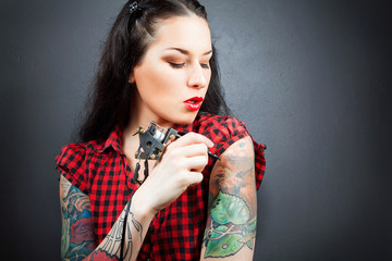 Photo of beautiful girl with tattoos and tattoo machine.
