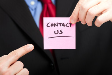 Businessman showing the words contact us