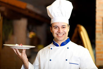 Chef holding a dish in a restaurant