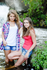 Two teen girls and summer outdoors near waterfall