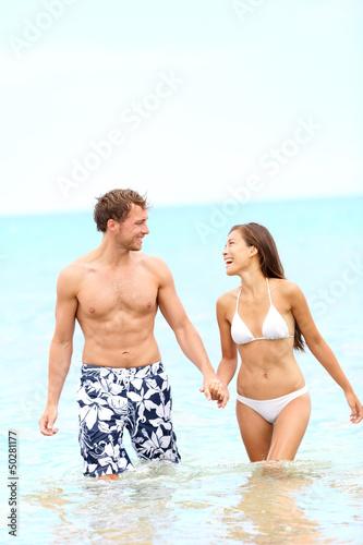 Couple on beach walking in water