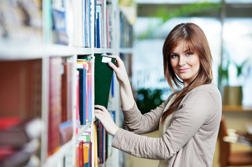 young student selecting book in library